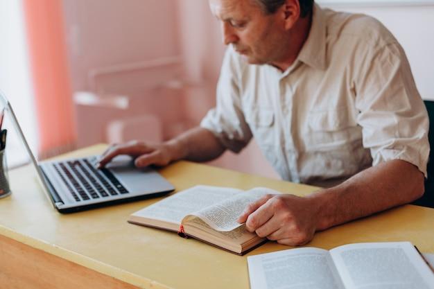 Lehrer, der mit offenem lehrbuch und laptop und arbeiten sitzt.