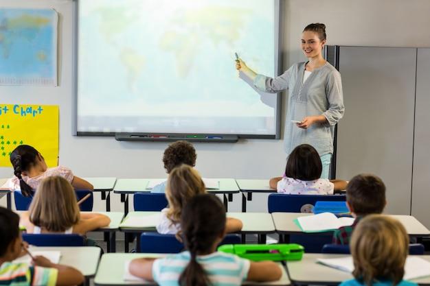 Lehrer, der schulkinder unter verwendung der projektionswand unterrichtet