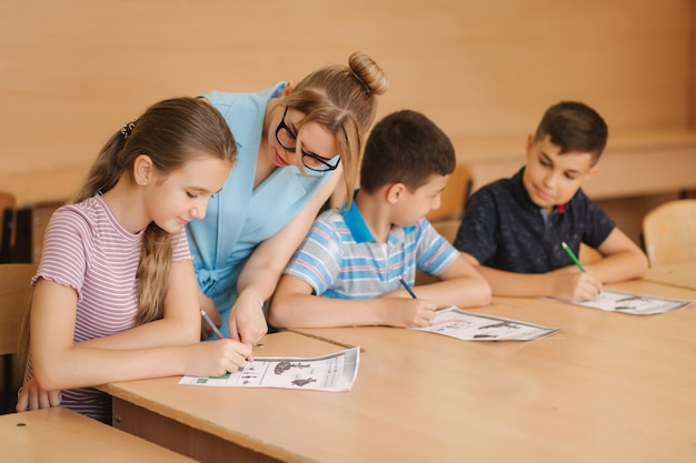 Lehrer, der schulkindern hilft, test im klassenzimmer zu schreiben. bildung, grundschule, lernen und