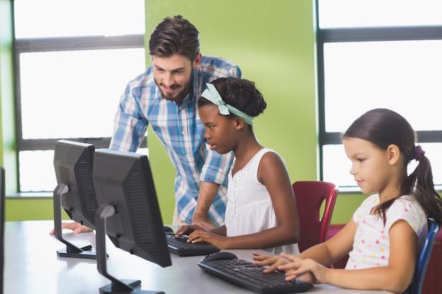 Lehrer, der schulmädchen beim lernen des computers unterstützt