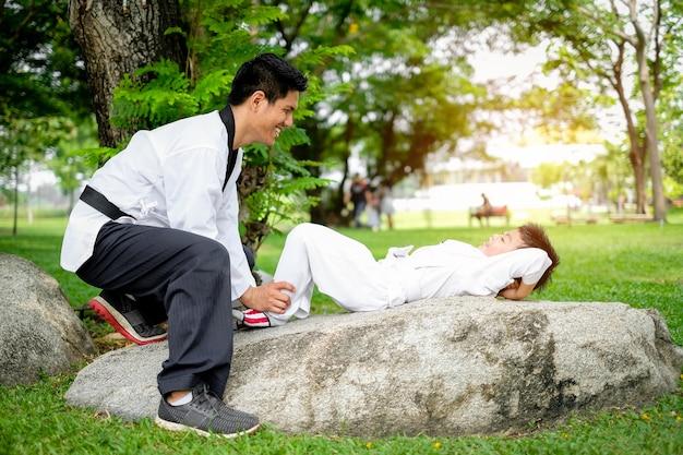 Lehrer, der taekwondo, kinderjunge unterrichtet, lernen taekwondo