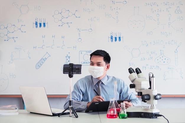 Lehrer der wissenschaftschemie, der maske trägt und online mit smartphone im klassenzimmer unterrichtet