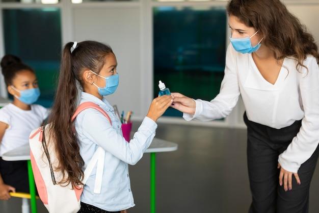 Lehrer desinfiziert die hände ihres schülers im unterricht