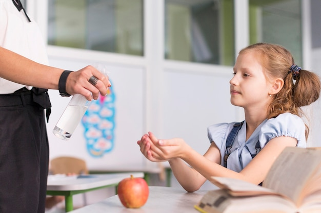 Lehrer desinfiziert die hände ihres schülers