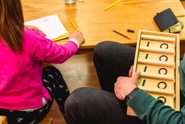 Lehrer, die mathekindern studenten zeigen, die montessori materialien verwenden.