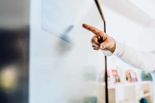 Lehrer erklärt seinen schülern einige ideen auf einem touch-tv.
