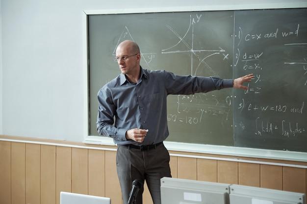 Lehrer für algebra, der auf tafel mit formeln und grafiken zeigt