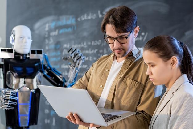 Lehrer für computertechnologien oder programmierer bei der präsentation eines automatisierungsroboters, der mit hilfe einer speziellen software betrieben wird