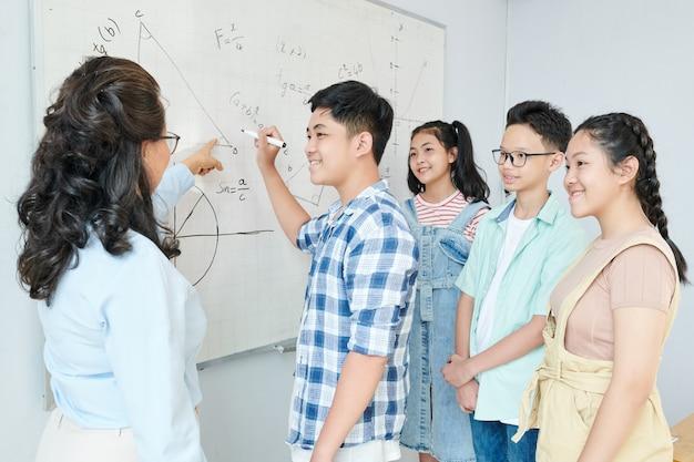 Lehrer für naturwissenschaften, der einer gruppe von schülern den satz erklärt und den schüler auffordert, eine gleichung auf ein whiteboard zu schreiben