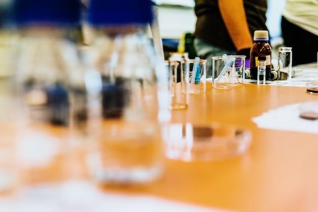 Lehrer für naturwissenschaften in einem klassenzimmer, die ihren schülern experimente in reagenzgläsern zeigen.