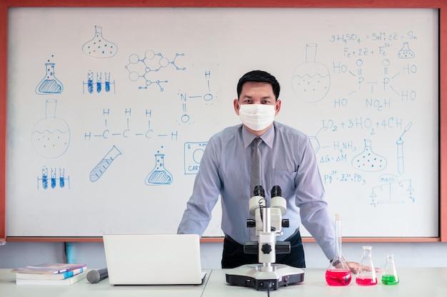 Lehrer für naturwissenschaftliche chemie unterrichtet mit mikroskop und laptop im klassenzimmer