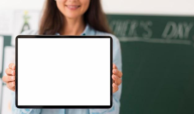 Lehrer hält eine tafel mit leerem bildschirm