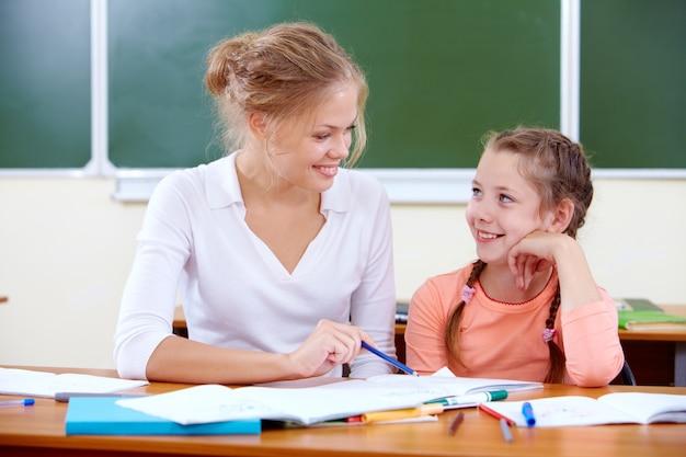 Lehrer helfen jungen mädchen mit dem schreiben lektion