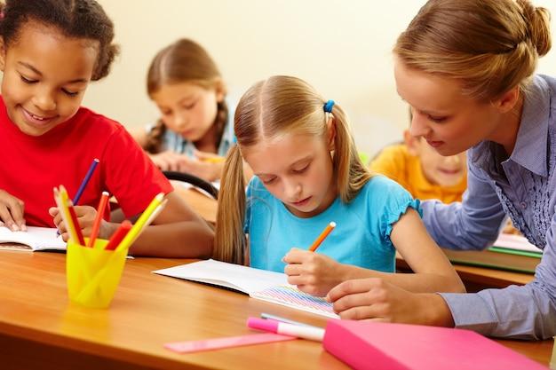 Lehrer helfen student mit schriftlichen arbeiten