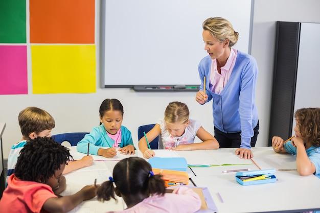 Lehrer hilft kindern bei ihren hausaufgaben im klassenzimmer