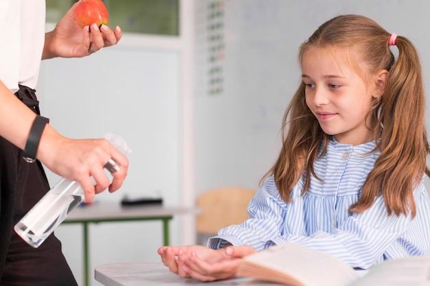 Lehrer hilft mädchen, ihre hände zu desinfizieren