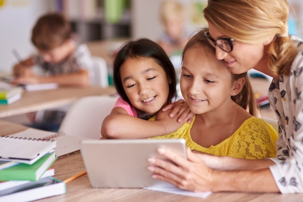 Lehrer hilft schülern mit digitalem tablet