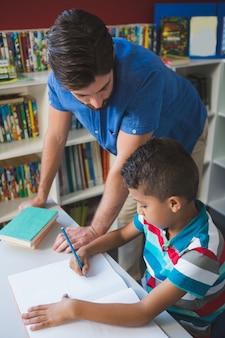 Lehrer hilft schulkind mit seinen hausaufgaben in der bibliothek