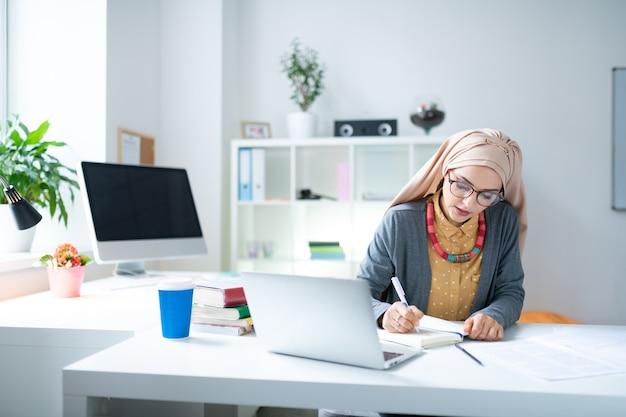 Lehrer in der nähe von laptop. junge muslimische lehrerin mit brille sitzt in der nähe eines laptops und schreibt notizen