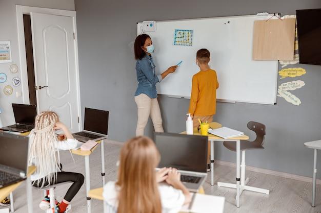 Lehrer in einer maske, der nahe der tafel steht und junge unterrichtet