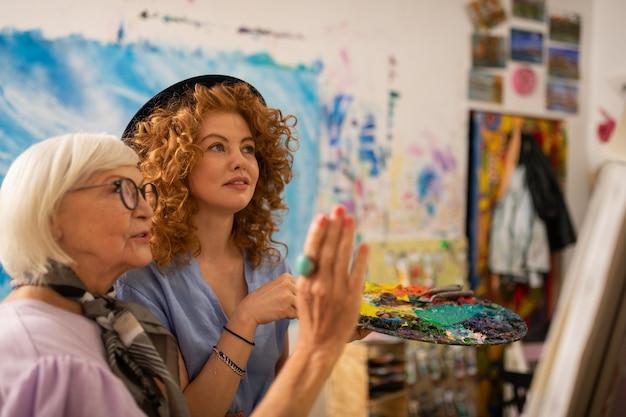 Lehrer in gläsern. kunstlehrerin in brille zufrieden mit der arbeit ihrer jungen rothaarigen schülerin