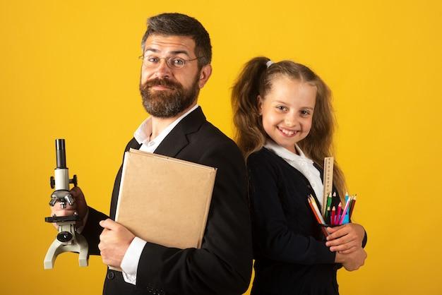 Lehrer mit glücklichem schülerschulmädchen porträt des lustigen schulmädchens und des tutors mit schulmaterial. glückliches lehrer- und studentenmädchen auf gelb. zurück zur schule, studentin in uniform.