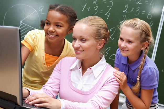 Lehrer mit ihren schülern auf dem laptop
