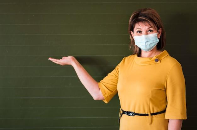 Lehrer mit maske am kreideboar erklären