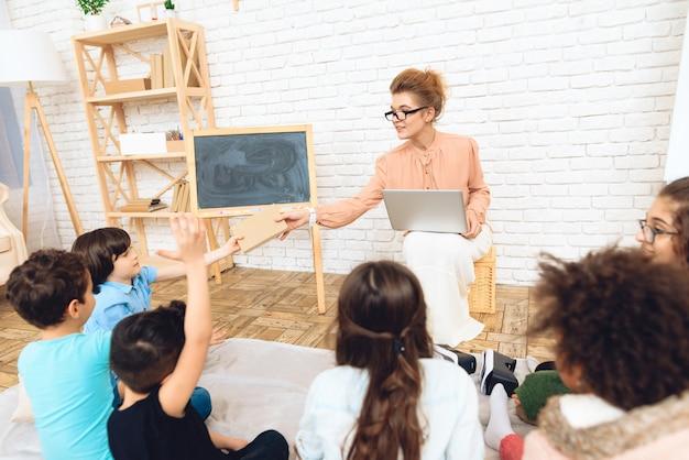Lehrer mit schauspielen gibt dem studenten buch, der auf boden sitzt