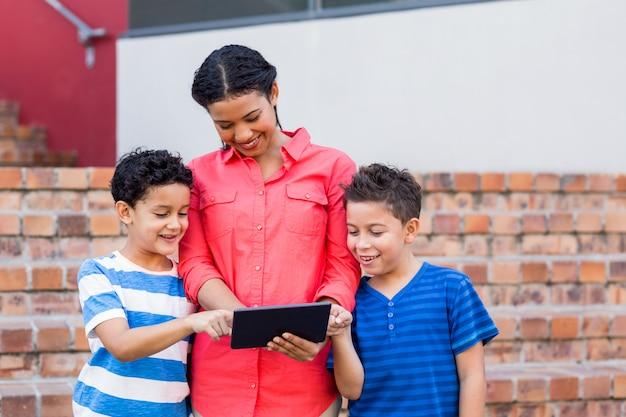 Lehrer mit schülern, die digitales tablet verwenden