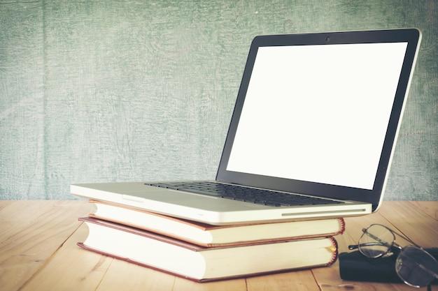 Lehrer- oder studentenschreibtisch auf schultafelhintergrund. bildungshintergrund.