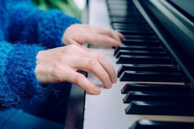 Lehrer pianist musiker probt klassische musik. professioneller musiker-lebensstil in innenräumen. nicht erkennbare frau, die klavier spielt. detail der weiblichen hände, die eine tastatur zu hause berühren.