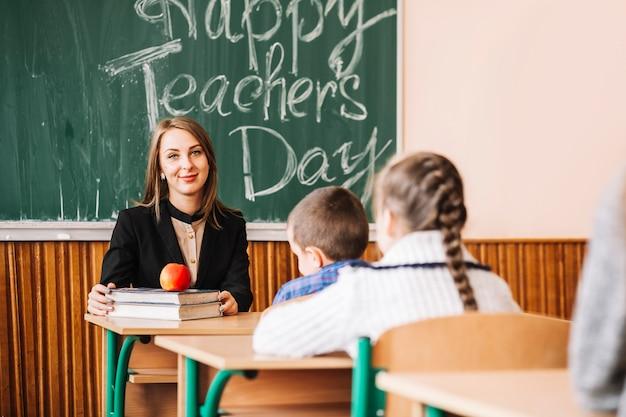 Lehrer sitzt am tisch