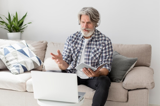 Lehrer spricht am laptop, der notizbuch hält