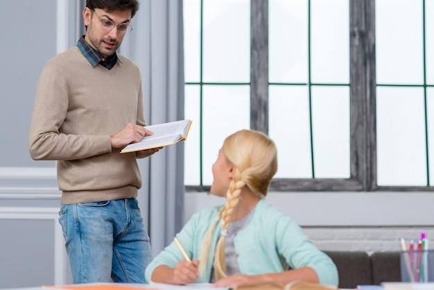 Lehrer stehend und kind hört ihm zu