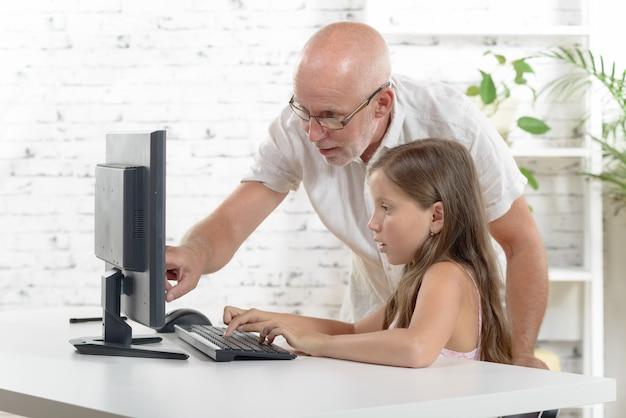 Lehrer und ein schulmädchen mit einem computer