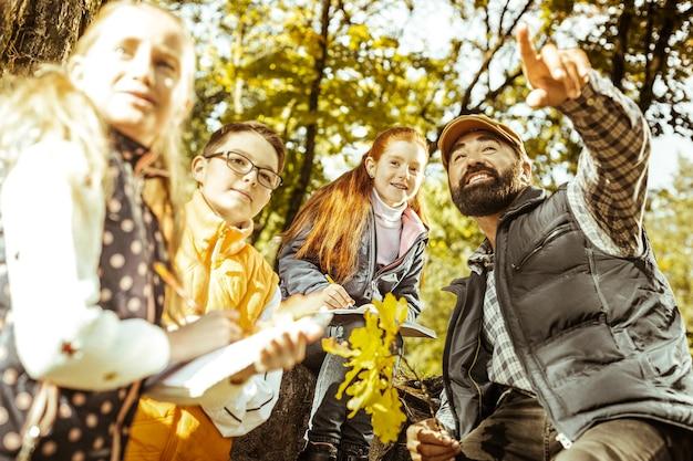 Lehrer und gruppe von freunden, die an einem sonnigen tag eine ökologiestunde im wald haben