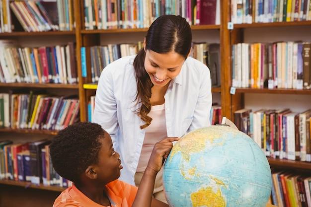 Lehrer und junge, die kugel in der bibliothek betrachten