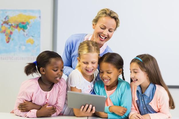 Lehrer und kinder mit digitalem tisch