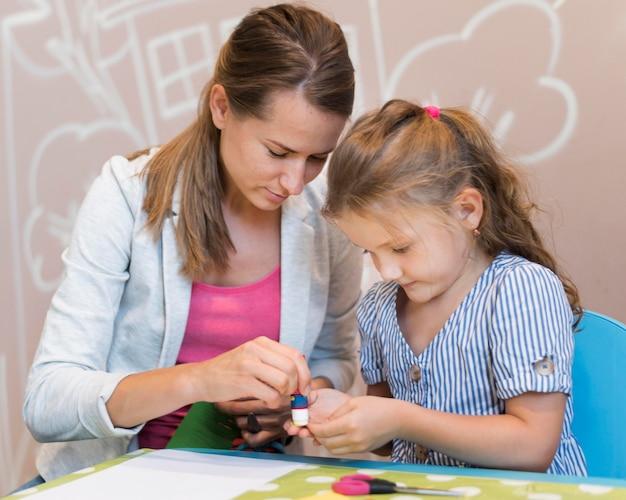 Lehrer und mädchen kleben papier zusammen