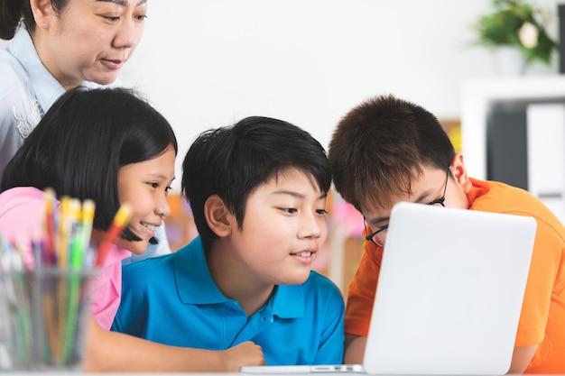 Lehrer und nette asiatische kinder, die zusammen laptop-computer verwenden.