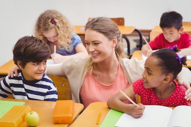 Lehrer und schüler arbeiten am schreibtisch zusammen