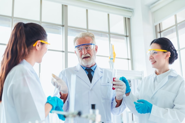 Lehrer und schüler arbeiten im team mit chemikalien im labor