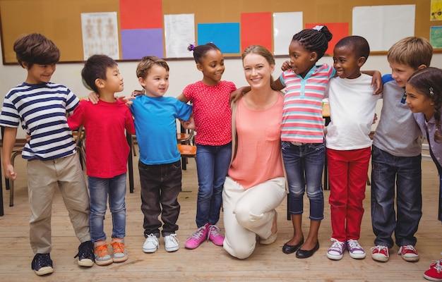 Lehrer und schüler, die an der kamera im klassenzimmer lächeln