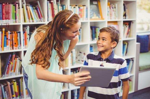 Lehrer und schuljunge, der digitale tablette in der bibliothek verwendet