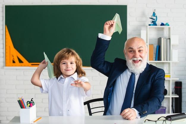 Lehrer und schuljunge mit papierfliegerpädagoge und schüler, die spaß daran haben, fürsorgliche lernende zu entwickeln ...
