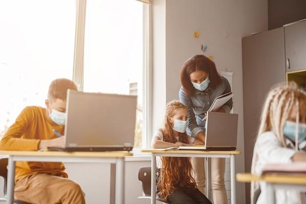 Lehrer und schulmädchen, die in der klasse auf den laptopbildschirm schauen