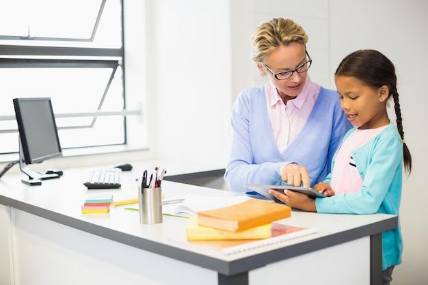 Lehrer und schulmädchen mit digitalem tablet