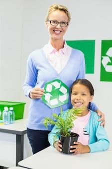Lehrer und schulmädchen mit recycling-logo im klassenzimmer