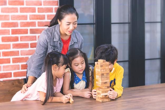 Lehrer und studenten bauen spielzeugblockturm
